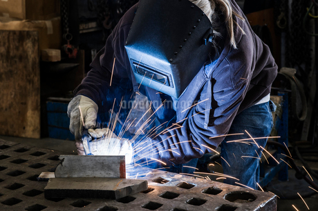 Factory worker using Oxyacetylene gas to weld two piece of metal in a sheet metal factoryの写真素材 [FYI02263161]