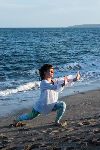 Young woman with brown hair wearing white blouse standing on a beach by the ocean, doing Tai Chi.の写真素材 [FYI02263165]