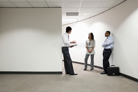 A mixed race group of three businesspeople standing and talking in an office hallway.の写真素材 [FYI02263178]