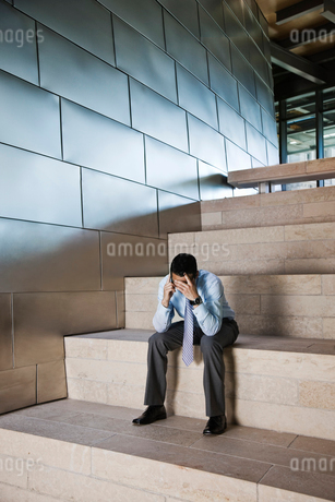 Businessman in a stressful situation while on a cell phone in the lobby of a large office building.の写真素材 [FYI02263185]