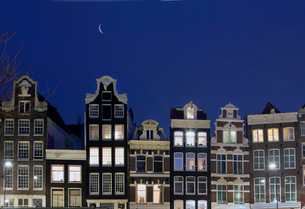 Row of illuminated traditional Dutch gable houses at night.の写真素材 [FYI02263188]
