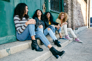 Four young women with curly hair sitting side by side on steps outside a building.の写真素材 [FYI02263191]