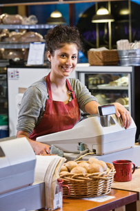 Caucasian woman employee at the cash register of a bakery/coffee shop.の写真素材 [FYI02263194]