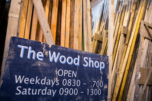 Close up of old blue Open sign for Wood Shop leaning against a stack of wooden planks.の写真素材 [FYI02263196]