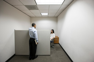 A black businessman talking to an Asian businesswoman working in a small corner cubicle office.の写真素材 [FYI02263202]