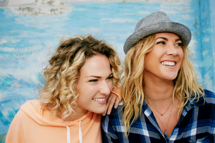 Portrait of two smiling women with blond hair wearing pink hoodie, blue checked shirt and grey Trilbの写真素材 [FYI02263218]