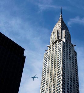 Low angle view of Chrysler Building, Manhattan, New York, USA, with passenger plane flying past.の写真素材 [FYI02263223]