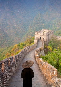Rear view of man wearing traditional straw hat standing on Great Wall of China.の写真素材 [FYI02263227]