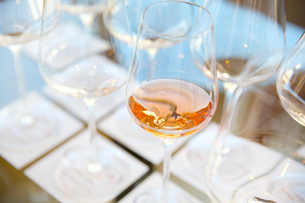 High angle close up of wine glasses in a row, one containing Rose wine.の写真素材 [FYI02263231]