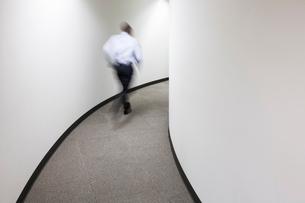 A blur of a businessman running in an office hallway.の写真素材 [FYI02263240]