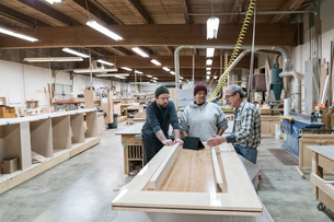 A group of mixed race carpenters discussing a project at a work station in a large woodworking shop.の写真素材 [FYI02263241]