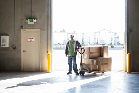 Male warehouse worker standing next to a manual pallet jack and cardboard boxes in a distribution waの写真素材 [FYI02263244]