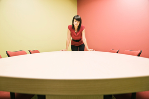 Caucasian woman in a conference room standing leaning on a table, confident pose.の写真素材 [FYI02263245]