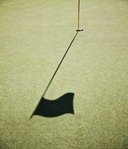 Shadow of a golf flag on the green of a golf course.の写真素材 [FYI02263248]