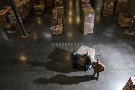 A group of three warehouse workers standing in the centre of a distribution warehouse.の写真素材 [FYI02263251]