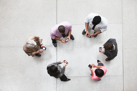 View looking down on a group of business people in a lobby area using their cell phones.の写真素材 [FYI02263253]