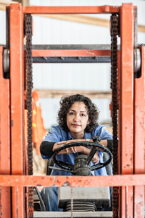 Hispanic woman employee using a forklift in a landscape company.の写真素材 [FYI02263255]