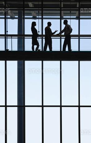 Business people meeting on an elevated walkway between office buildings.の写真素材 [FYI02263264]
