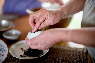 Close up of woman standing at a table in a kitchen, making sushi.の写真素材 [FYI02263265]