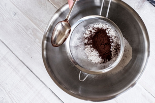 A metal bowl with ingredients and a sieve with cocoa powder.の写真素材 [FYI02263272]