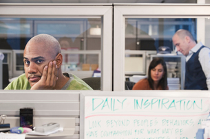 Black man in his office cubicle with co-workers in the background.の写真素材 [FYI02263276]