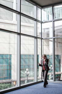 A Caucasian businesswoman talking on a cell phone while standing next to a large window in a conventの写真素材 [FYI02263277]