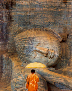 Rear view of man in orange robe standing in front of giant reclining Buddha sculpture carved from roの写真素材 [FYI02263281]