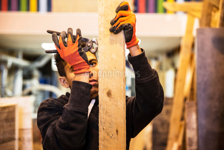 Young man wearing work gloves standing in warehouse, removing rusty nails from recycled wooden plankの写真素材 [FYI02263284]