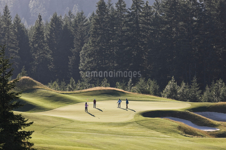 View from above of four golfers playing golf on a green in the distance.の写真素材 [FYI02263290]