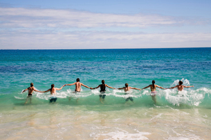 Rear view of group of people holding hands, jumping into wave in ocean.の写真素材 [FYI02263294]