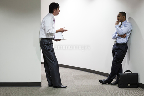 An Asian businessman and a black businessman talking over an issue while standing in an office hallwの写真素材 [FYI02263299]