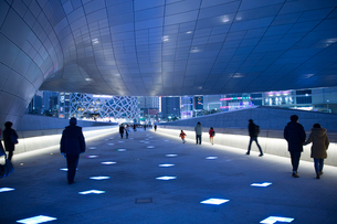 Rear view of people walking along illuminated walkway underneath curved ceiling of contemporary builの写真素材 [FYI02263301]
