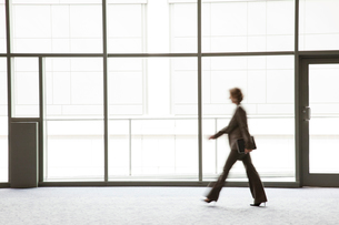 A businesswoman blurred in silhouette while walking past a large convention centre window.の写真素材 [FYI02263314]