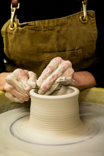 Close up of potter wearing apron working on pottery wheel, shaping clay vase.の写真素材 [FYI02263339]