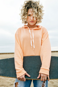 Young woman with curly blond hair wearing pink hoodie and ripped jeans standing on sandy beach, holdの写真素材 [FYI02263341]