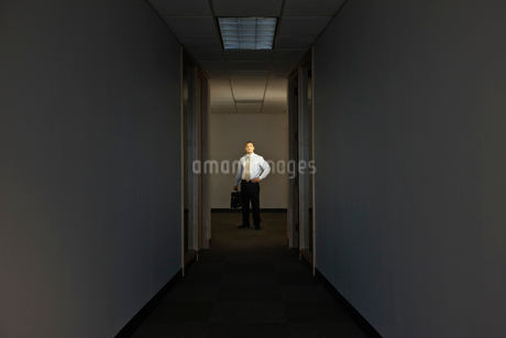 A portrait of a black businessman standing at the end of a long dark hallway.の写真素材 [FYI02263346]