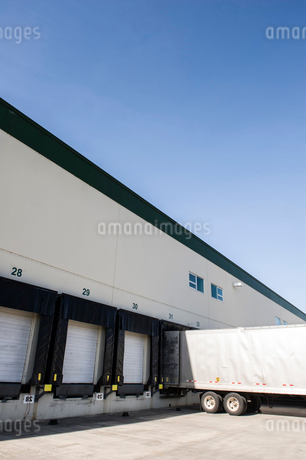Exterior view of a warehouse loading dock with a truck trailer pulled up to one of the doors.の写真素材 [FYI02263348]