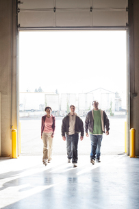 Three employees walking through the loading dock door of a distribution warehouse.の写真素材 [FYI02263352]