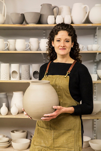 Woman with curly brown hair wearing apron holding unfired spherical clay vase.の写真素材 [FYI02263360]