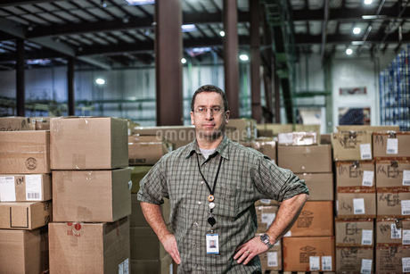 Portrait of a Caucasian warehouse worker in a large distribution warehouse, showing products storedの写真素材 [FYI02263361]