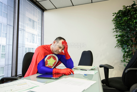 A middle aged Caucasian office super hero ponders the stress of the job.の写真素材 [FYI02263374]