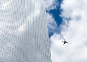 Low angle view of glass facade of contemporary skyscraper, passenger plane in cloudy sky.の写真素材 [FYI02263381]