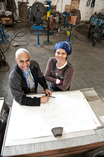 Black man owner of a sheet metal factory and a black woman factory worker going over plans at a workの写真素材 [FYI02263386]