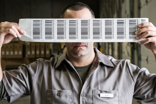 A warehouse worker holding up a sheet of bar code shipping labels in a distribution warehouse.の写真素材 [FYI02263387]