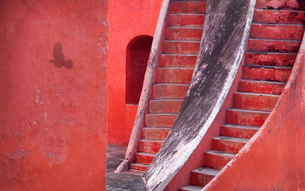 Close up of two steep stairway running parallel up a red building.の写真素材 [FYI02263399]