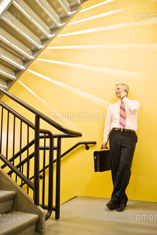 Caucasian man on the phone in an office stairwell.の写真素材 [FYI02263415]
