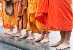 Low angle view of group of barefoot men wearing orange robes standing side by side on a pavement.の写真素材 [FYI02263418]