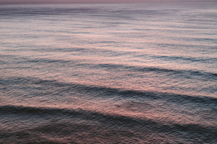 View from above of rolling waves advancing to the shore, a pattern on the water surface at dusk.の写真素材 [FYI02263421]