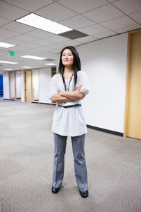 An Asian businesswoman standing alone in her office  space.の写真素材 [FYI02263422]