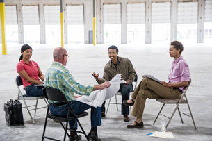 Multi-racial team of people going over plans for a new warehouse interior.の写真素材 [FYI02263424]